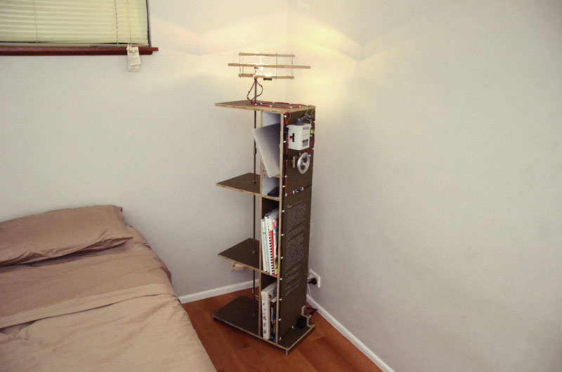 A combination floor lamp, book case, bedside table and charging station.