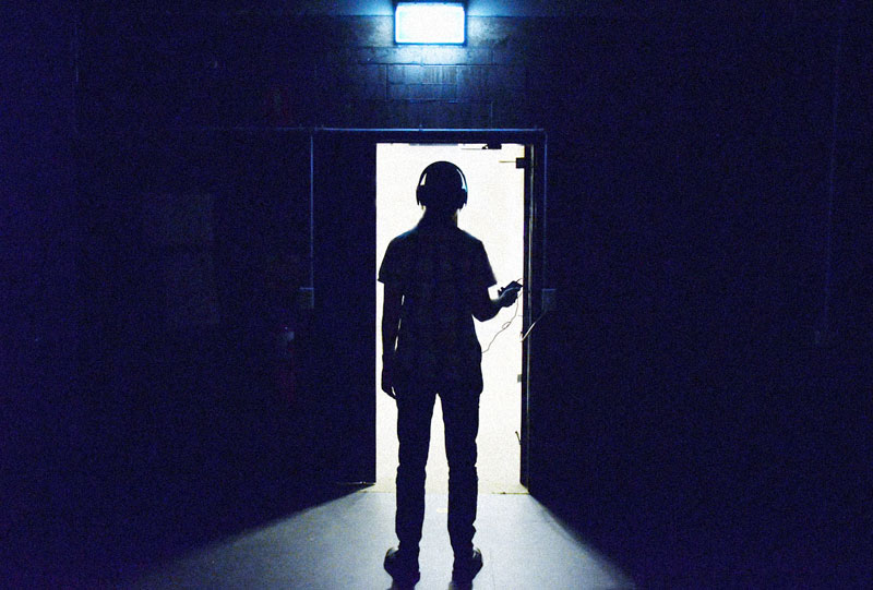 Photo of a man silhouetted in a doorway.